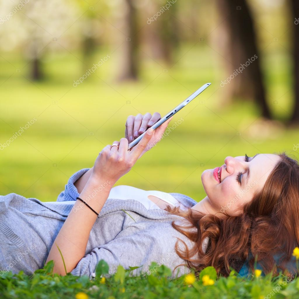 Young woman using her tablet computer while relaxing outdoors in a park on a lovely spring day