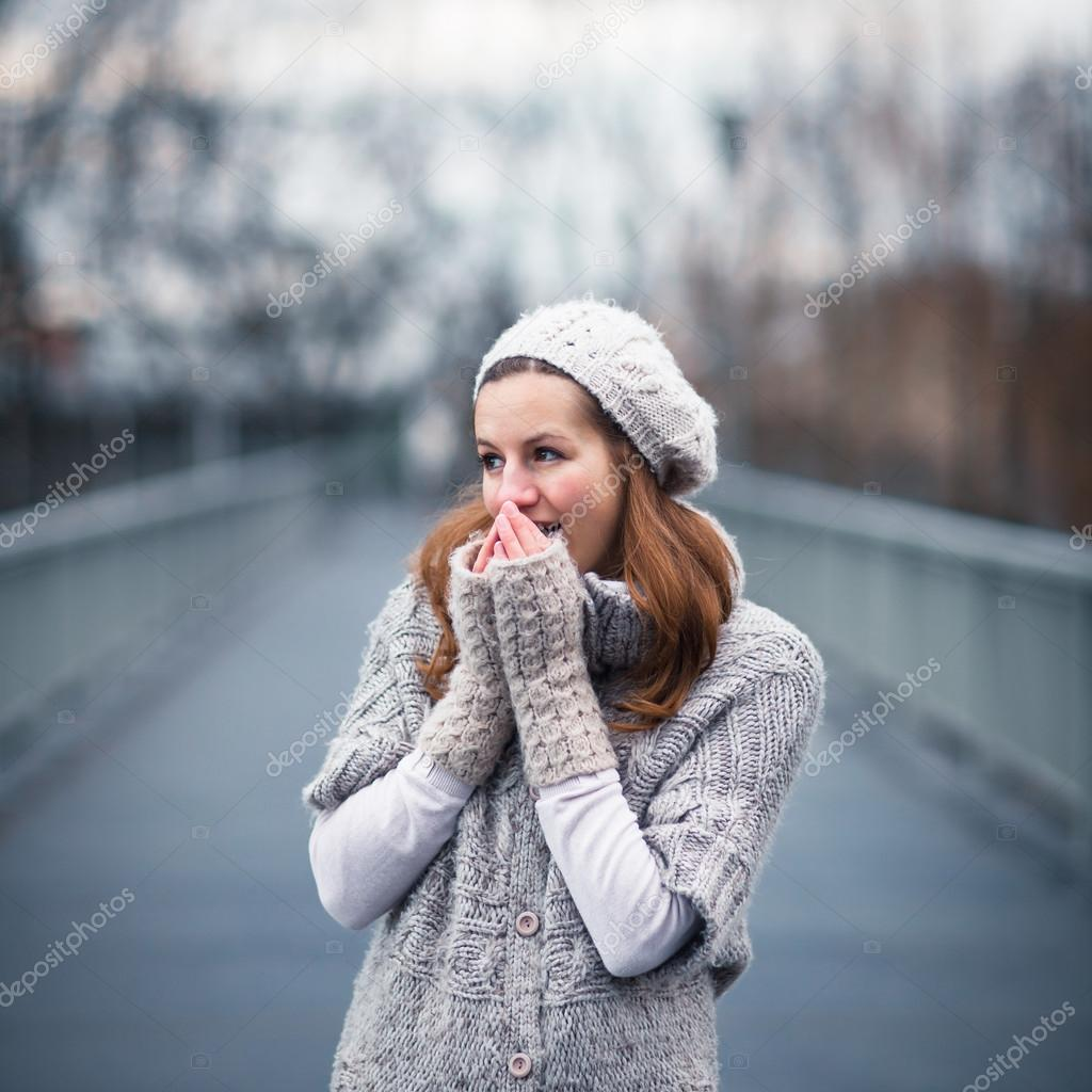 Autumn portrait: young woman dressed in a warm woolen cardigan posing outside in a city park