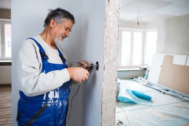 Senior man working on the electrical installations in a freshly
