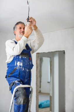 Senior man installing a bulb in a freshly renovated appartment stock vector
