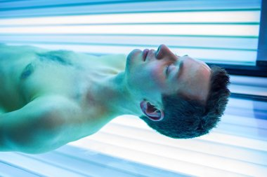 Handsome young man relaxing during a tanning session in a modern