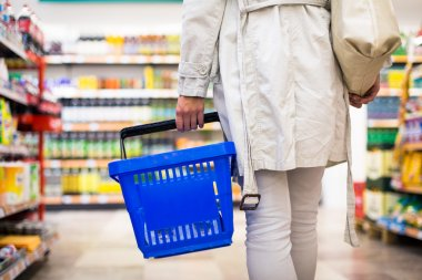 Pretty young woman buying groceries in a supermarket, mall, grocer