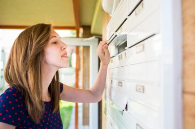 Woman checking her mailbox for new letters