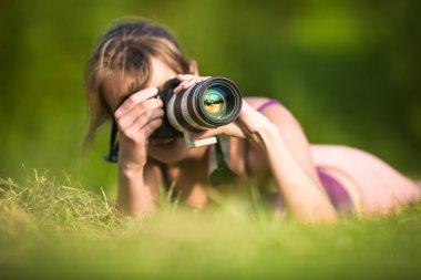 Pretty female photographer lying in grass