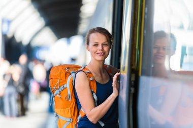 Woman in a trainstation, boarding a train