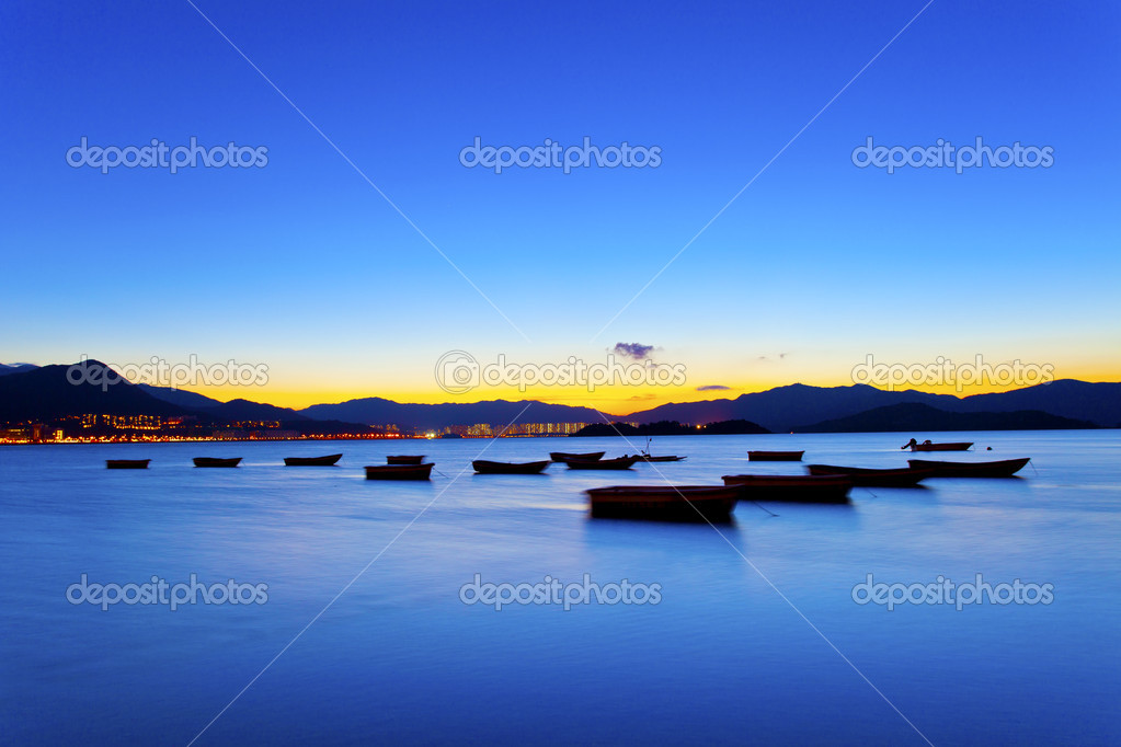 Sunset view by the coast with boats