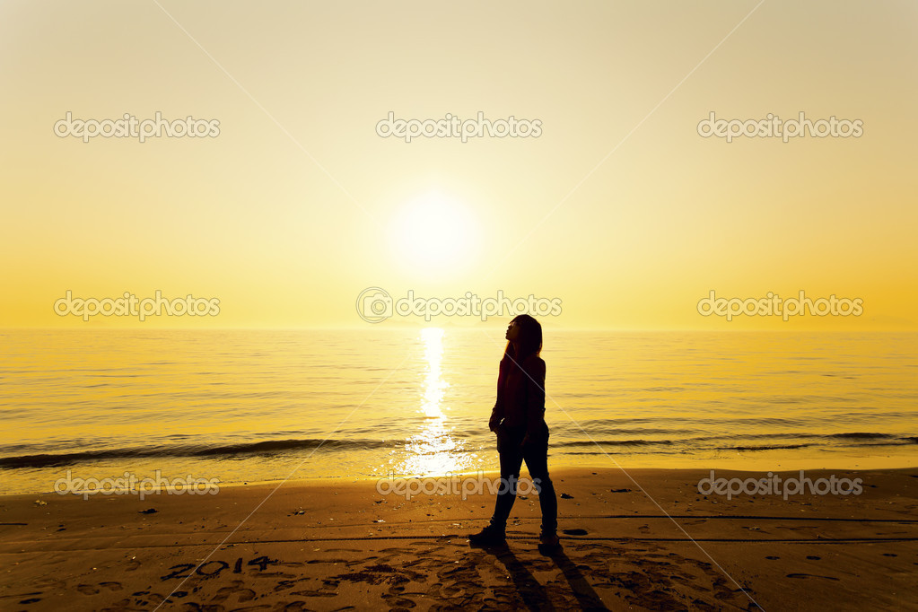 Young woman standing on beach under sunset
