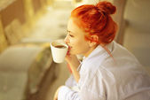 Good morning womans with cup of fragrant coffee