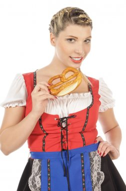 Blond young woman in dirndl eating pretzel