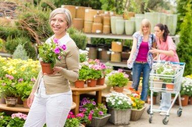 Garden center senior lady hold potted flower