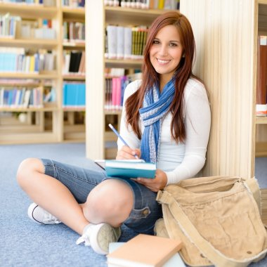 High school library smiling student with notepad