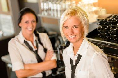 Cafe waitresses behind bar smiling at work