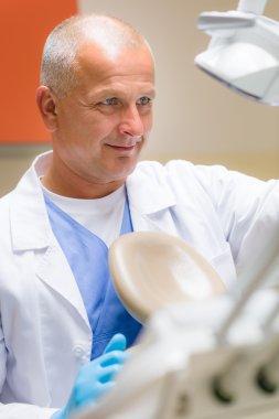 Male dental surgeon set up patient chair