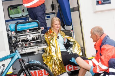 Paramedics with woman bike accident in ambulance