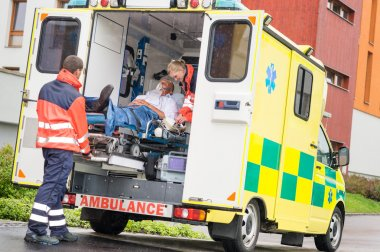 Paramedics putting patient in ambulance car aid
