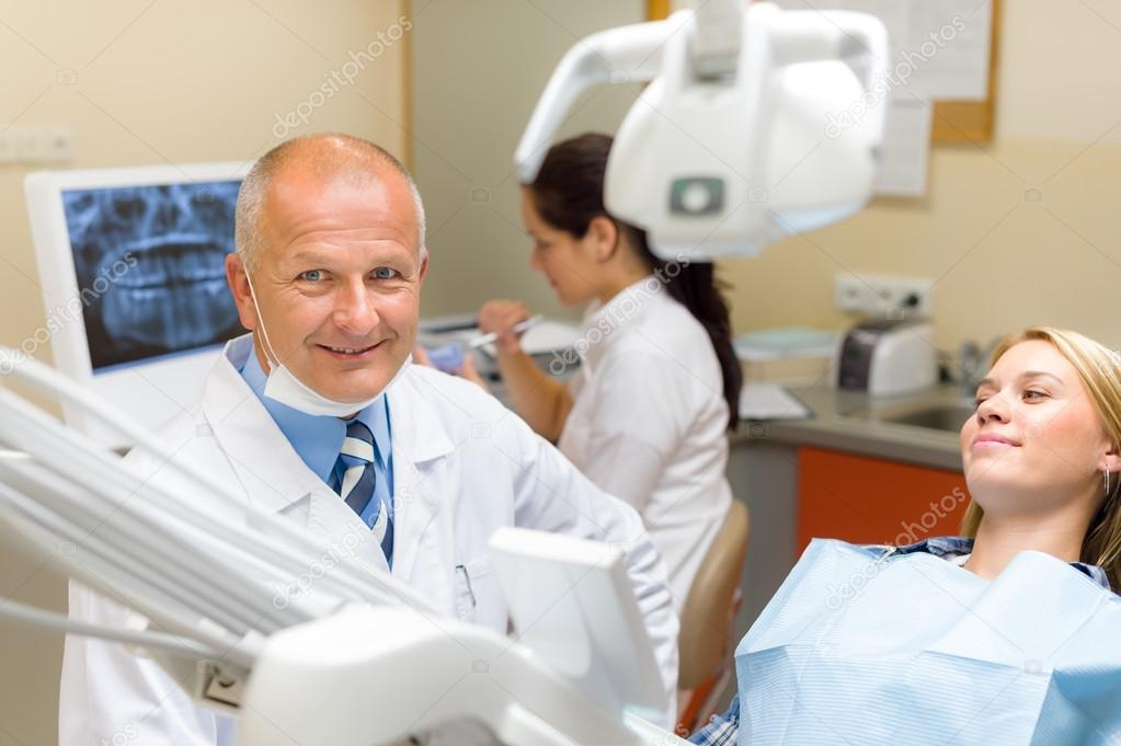 Friendly dentist with female patient dental office