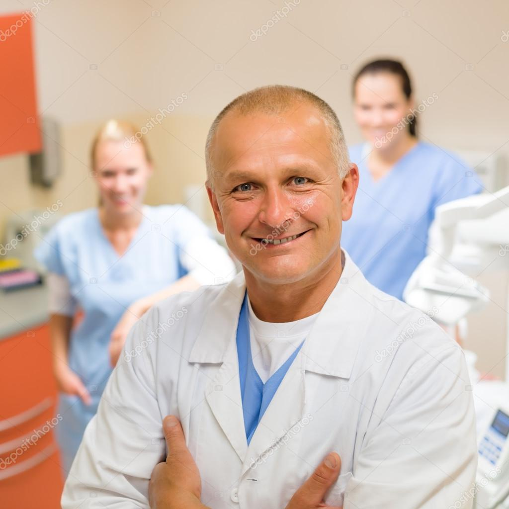 Smiling dental surgeon posing with nurses