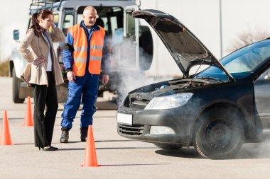Woman with technician help smoking car engine