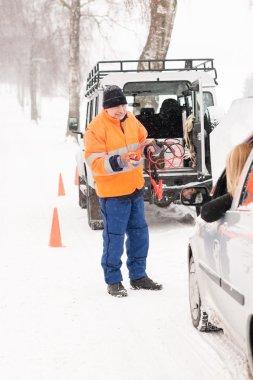 Man helping woman with broken car snow