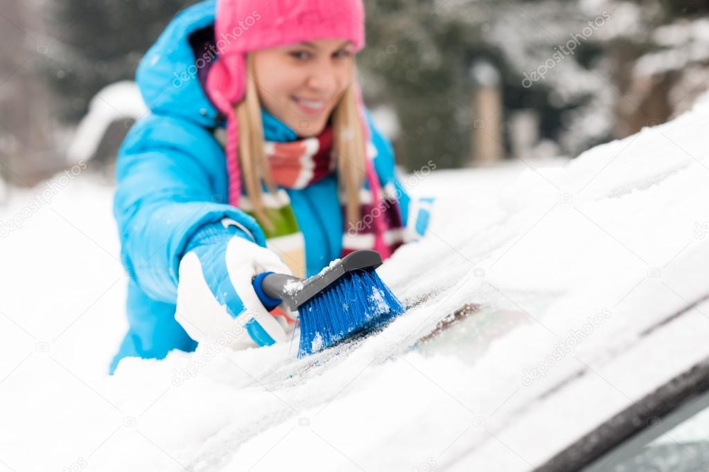 Woman wiping snow car window using brush