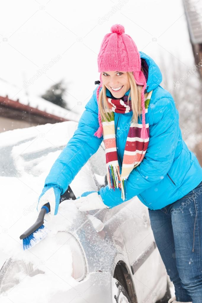 Woman cleaning car hood of snow brush