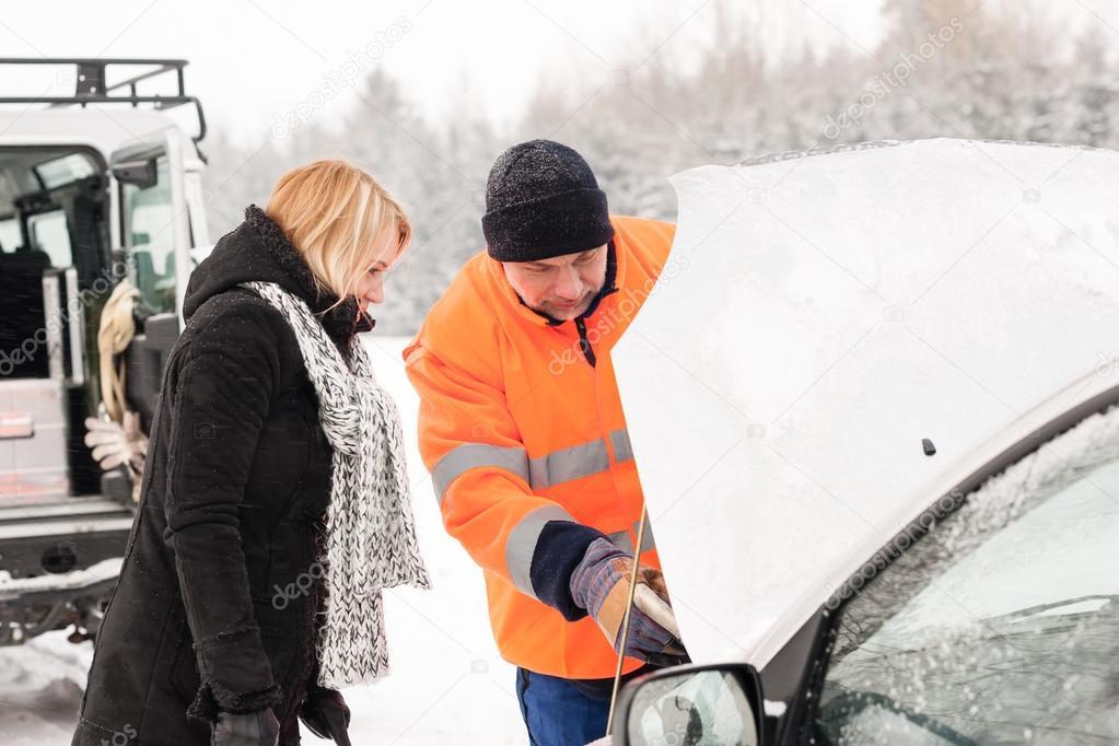 Woman mechanic looking under car hood snow