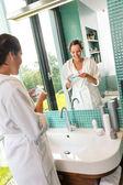 Mosolygó nő segítségével a bőr care lotion fürdőszoba