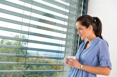Young woman day dreaming looking window blinds