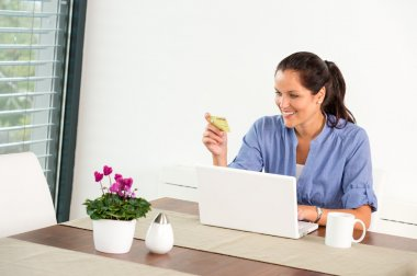 Cheerful woman internet home banking card laptop