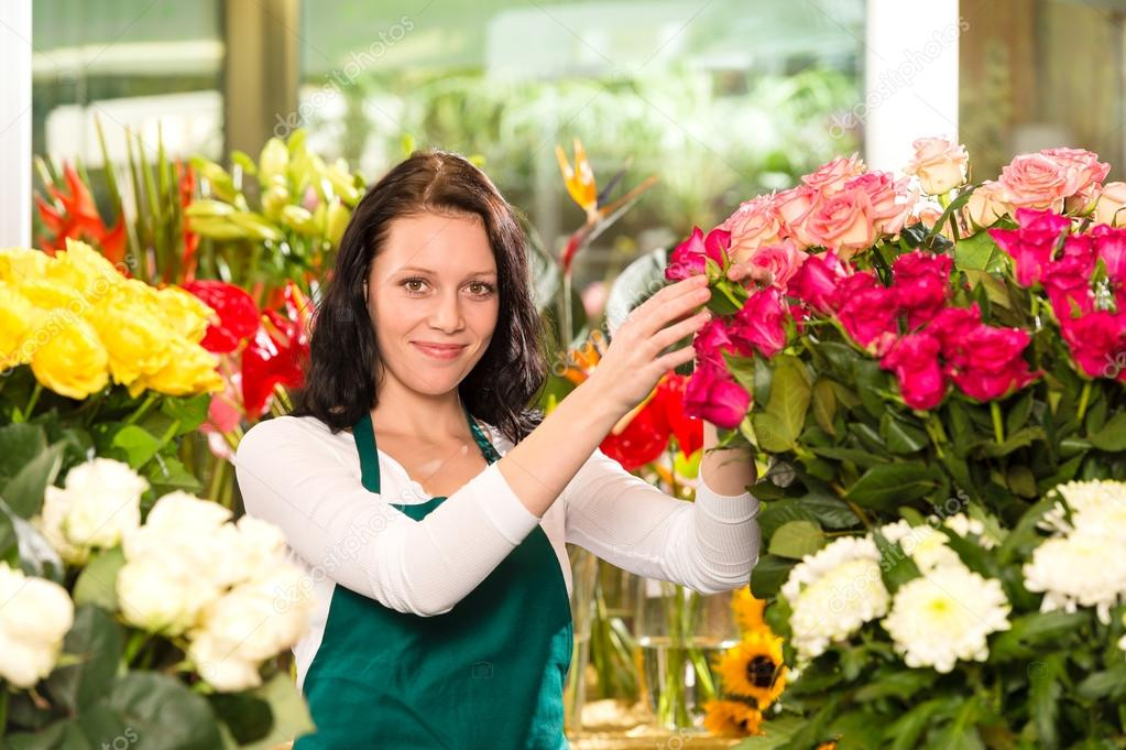 Happy young woman arranging flowers florist shop — stock