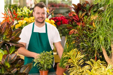 Happy male florist working flower gardening shop