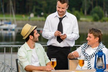 Smiling waiter taking order from men customers