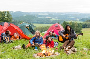 Camping students listening girl with guitar tents