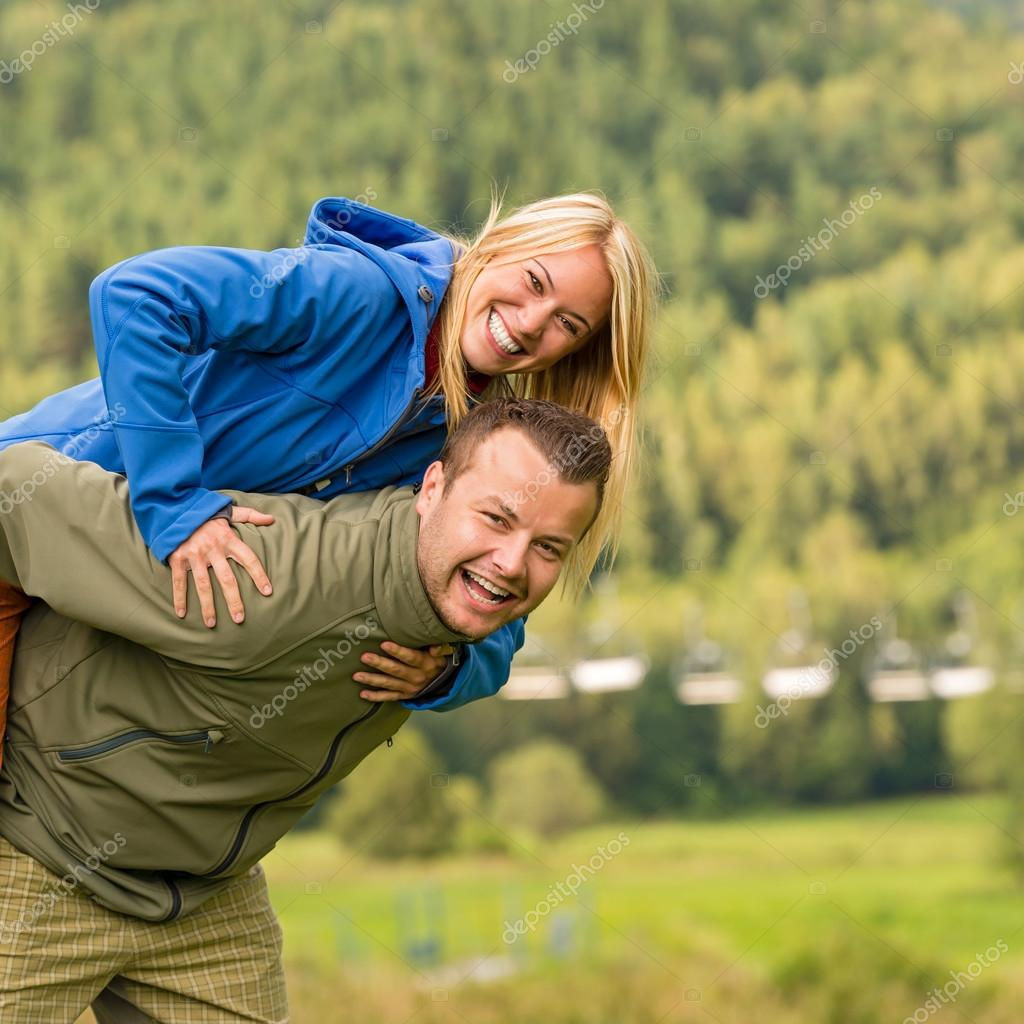 Couple having piggyback ride outside green nature