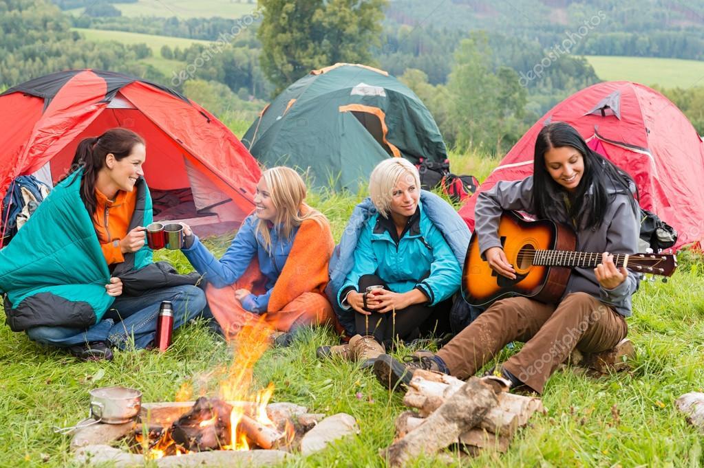 Beside campfire girls sitting listening to guitar