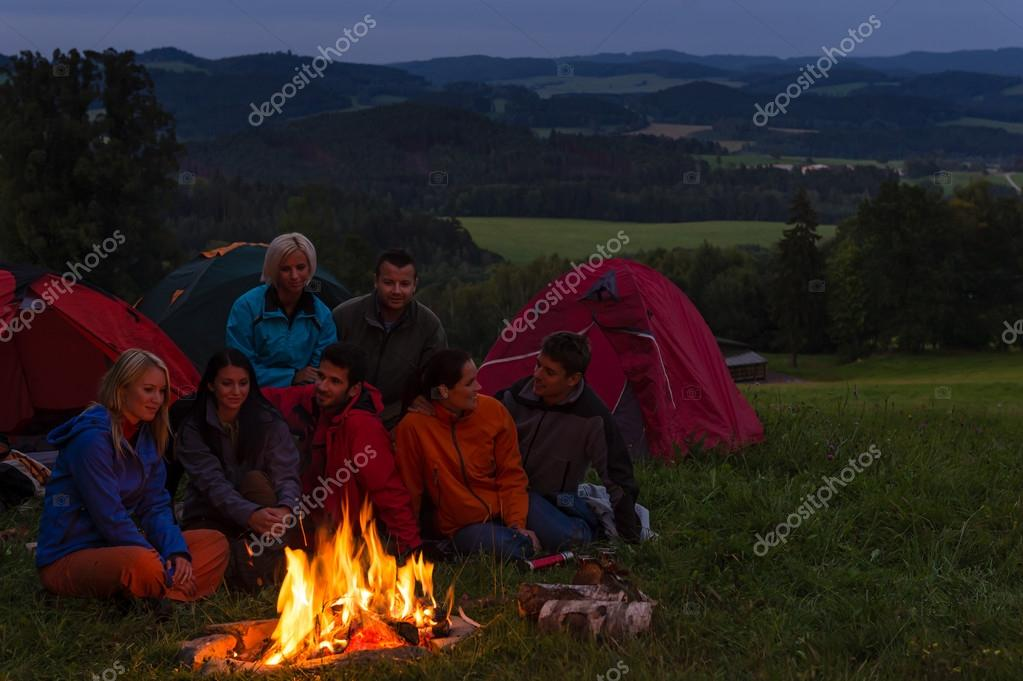 Camping watching campfire together beside tents