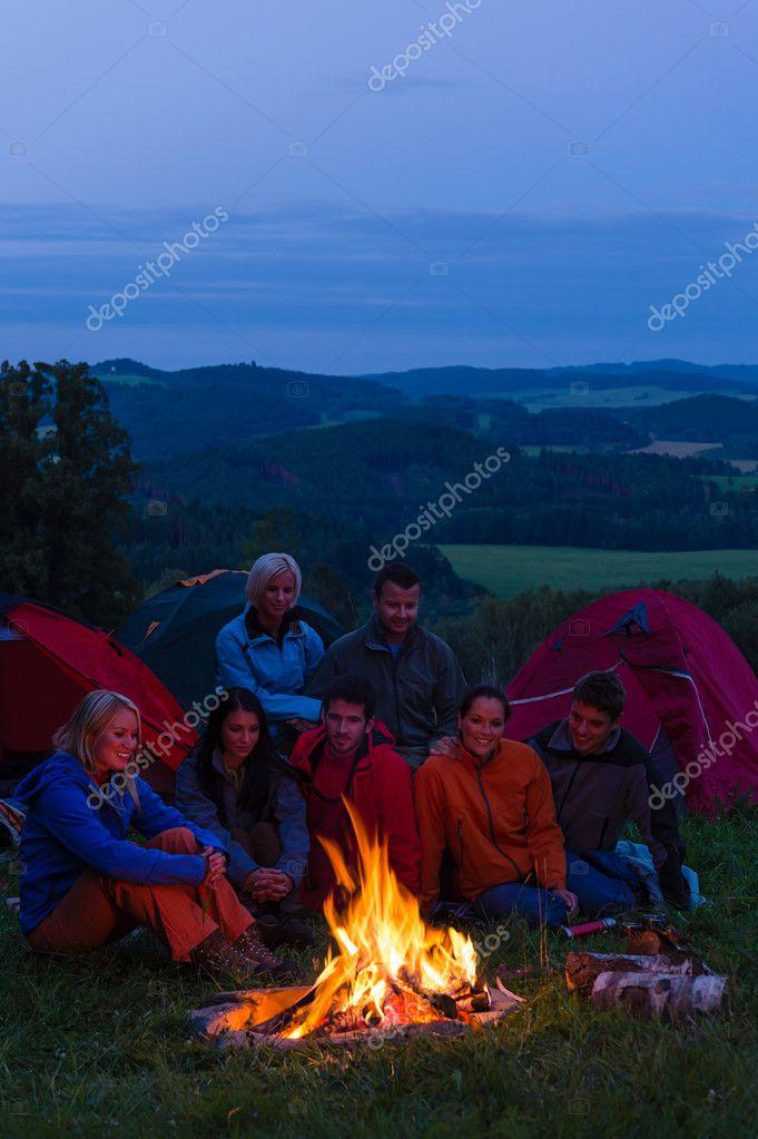 In dark camper friends sitting around fire