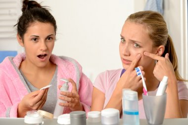Young teenagers with acne problem in bathroom