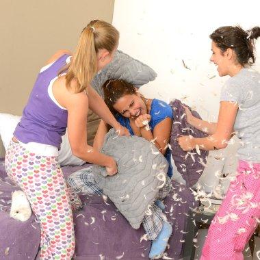 Teenager girls pillow fighting in bedroom