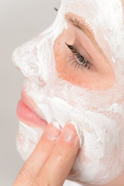 Fingers applying face mask moisturizer young girl