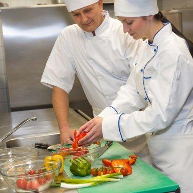 Cooks preparing salad in restaurant's kitchen