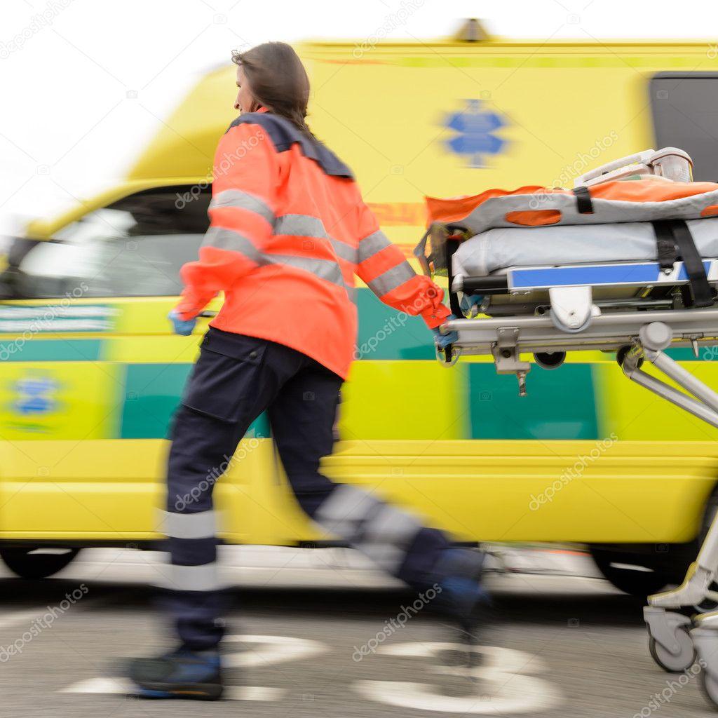Running blurry paramedic woman pulling gurney