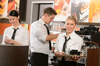 Confident waitresses and waiter working in bar