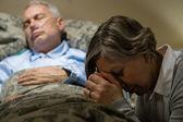 Uneasy senior woman praying for sick man