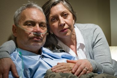 Anxious senior wife holding her sick husband