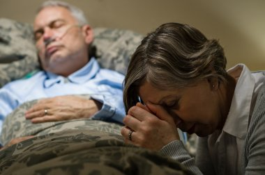 Senior woman praying for sick man sleeping in hospital bed stock vector