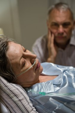 Dying woman in bed with caring man