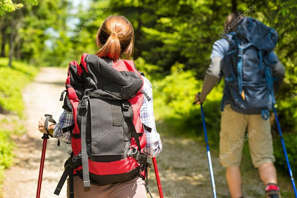 Tourist couple hiking in forest