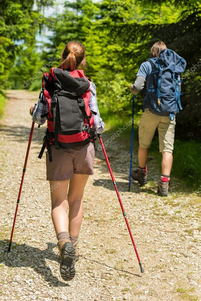 Young tourists with trekking poles in woods