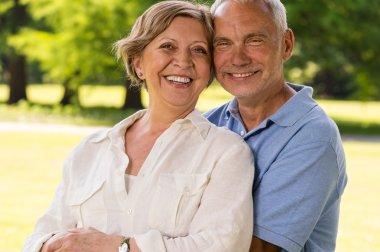 Senior citizen couple laughing outdoors